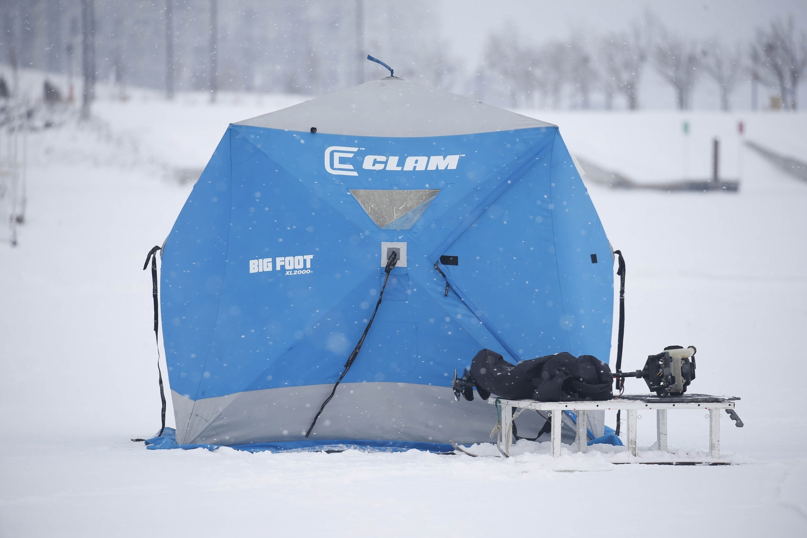 A portable heated shelter owned by Scott Chaplin, of Derby, sits next to his sled and gas-powered ice hole auger as he fishes inside.