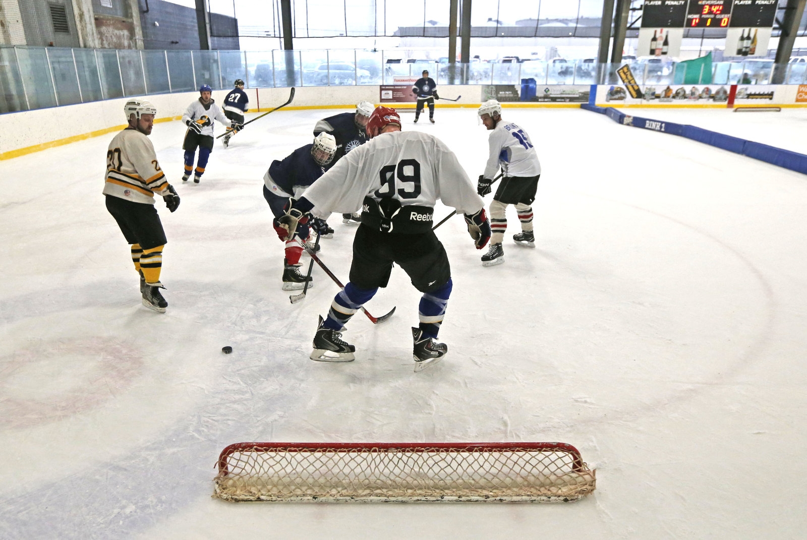 Members of the Buffalo DPW team, in dark blue, and The Ice Breakers tangle on the ice during play during the Pond Hockey event at RiverWorks.