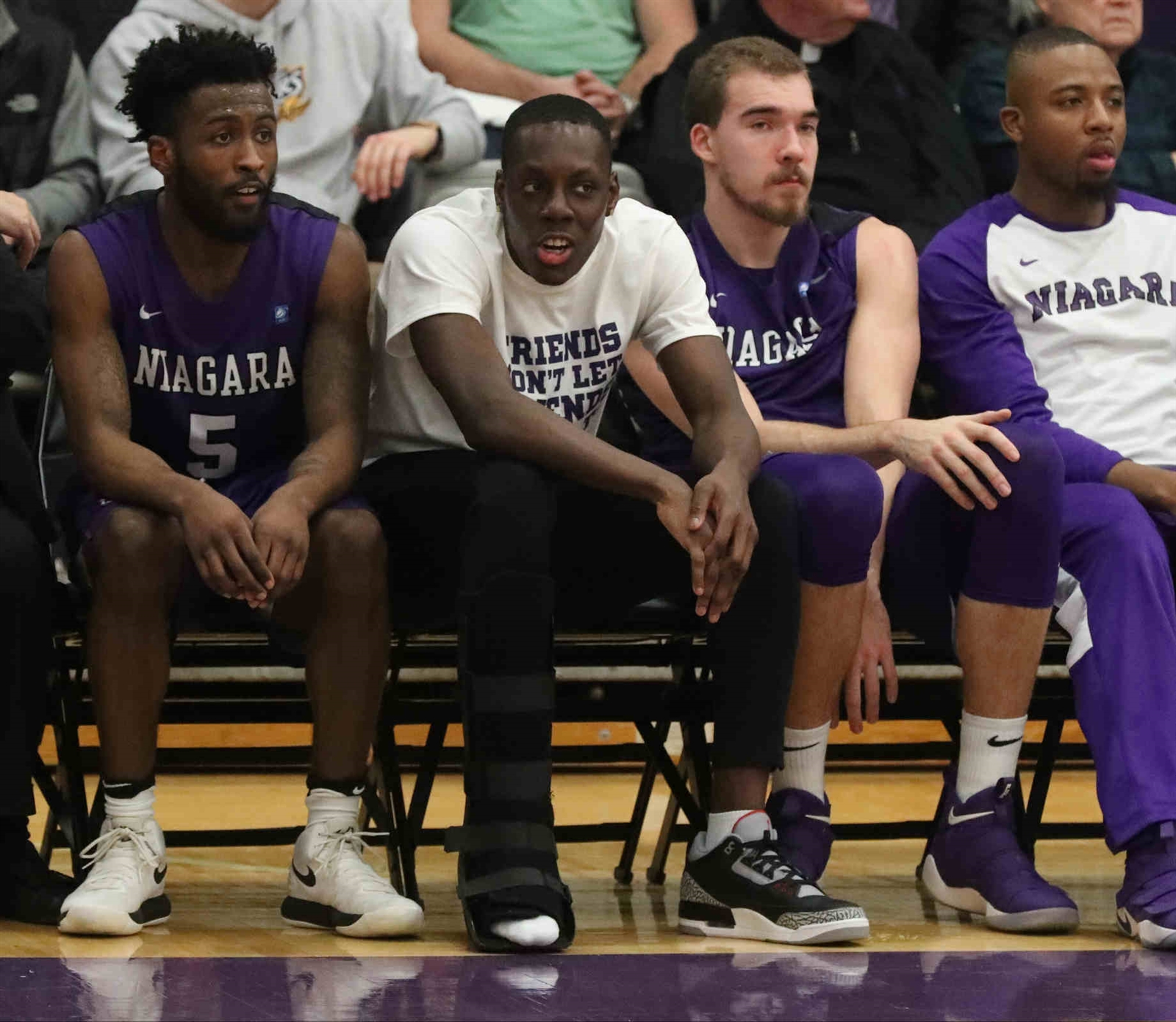 Niagara Purple Eagles guard Matt Scott (13) sits on the bench  with a boot on his foot.