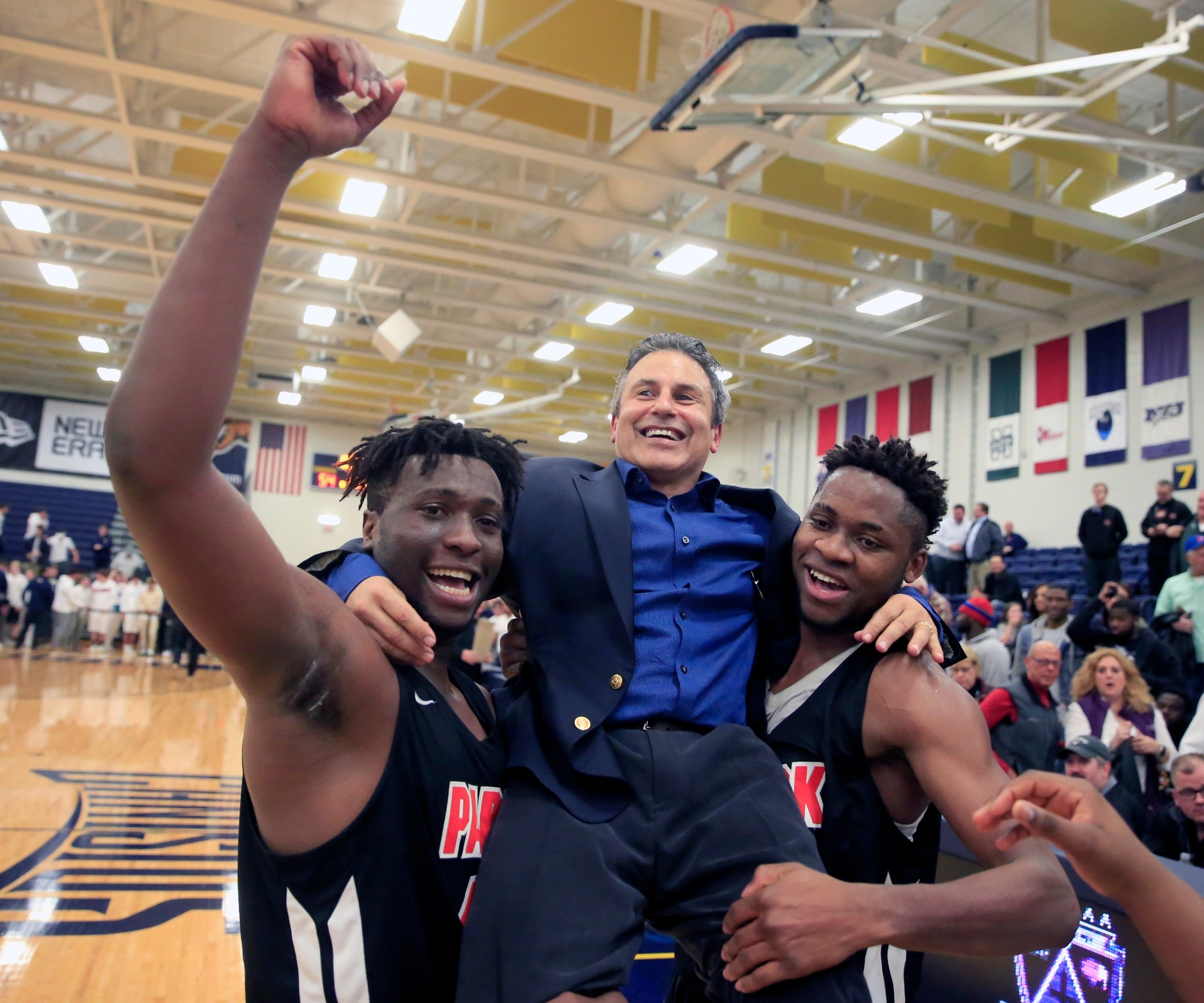 Park player Julian Eziukwu and Quentin Nnagbo lift head coach Rich Jacob in the air after defeating Canisius, 62-54, in the Class A final at the Koessler Center on Tuesday, Feb. 27, 2018.
