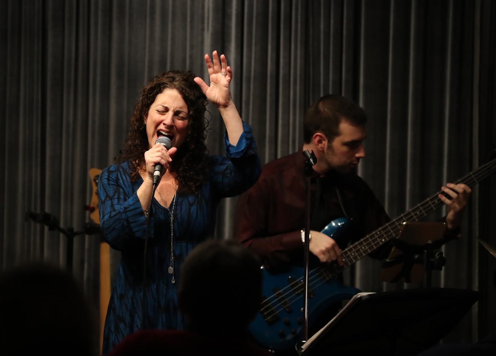 DeeAnn DiMeo Tompkins and her band perform Valentine's Day jazz songs, including songs made famous by Billie Holiday at Pausa Art House. Behind is bass guitar player Avery Weissman.