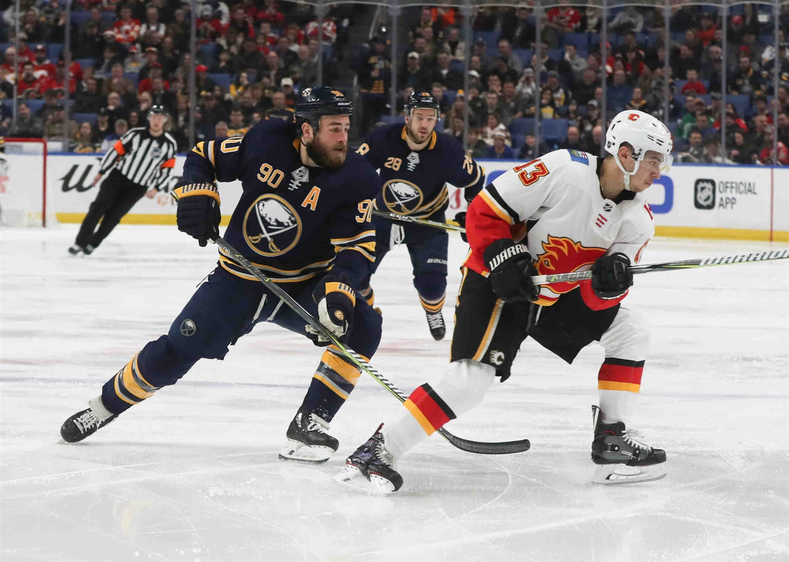 Buffalo Sabres center Ryan O'Reilly (90) skate with the puck past Calgary Flames left wing Johnny Gaudreau (13) in the first period.