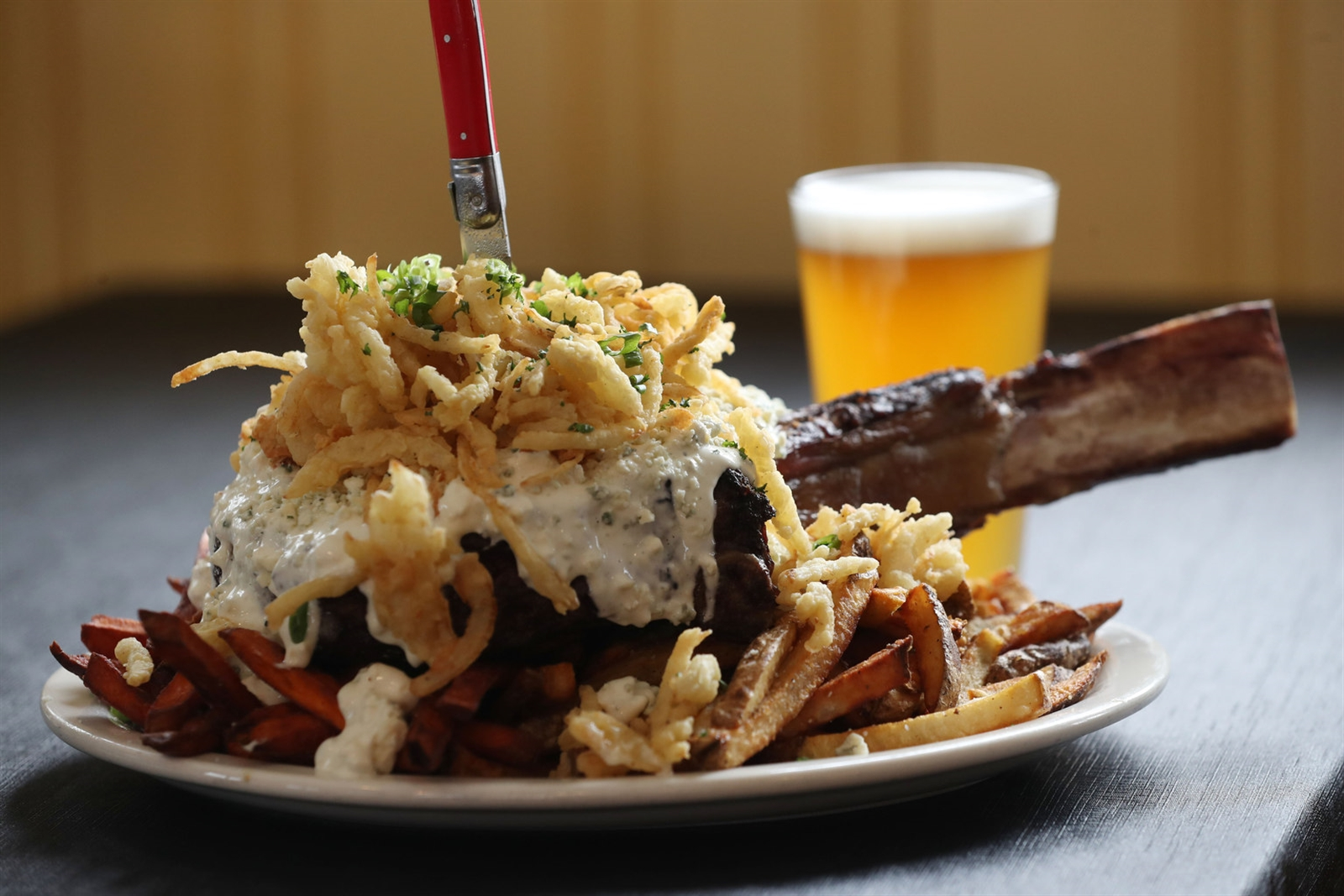 "Chaz Bulera's Bone-in-the-Stone is a 50-ounce bone-in rib-eye made famous on the Food Channel's ""Man Vs. Food.""  It comes with a pound of fresh cut fries, one pound of sweet potato fries and topping include creamy blue cheese, crumbled blue cheese and a pile of onion straws."