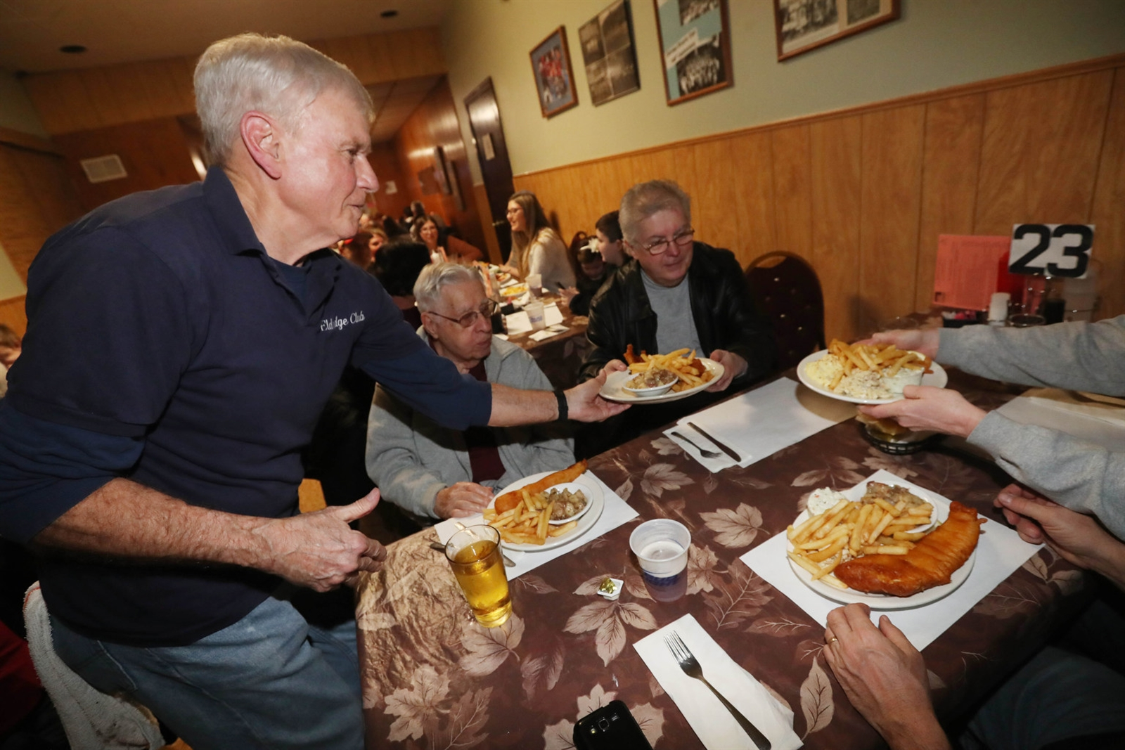 The Eldredge Bicycle Club's Art Marshall, left, serves fish fries to the Sylvester family. From left is Joseph Sylvester, 98, and his son Joseph.