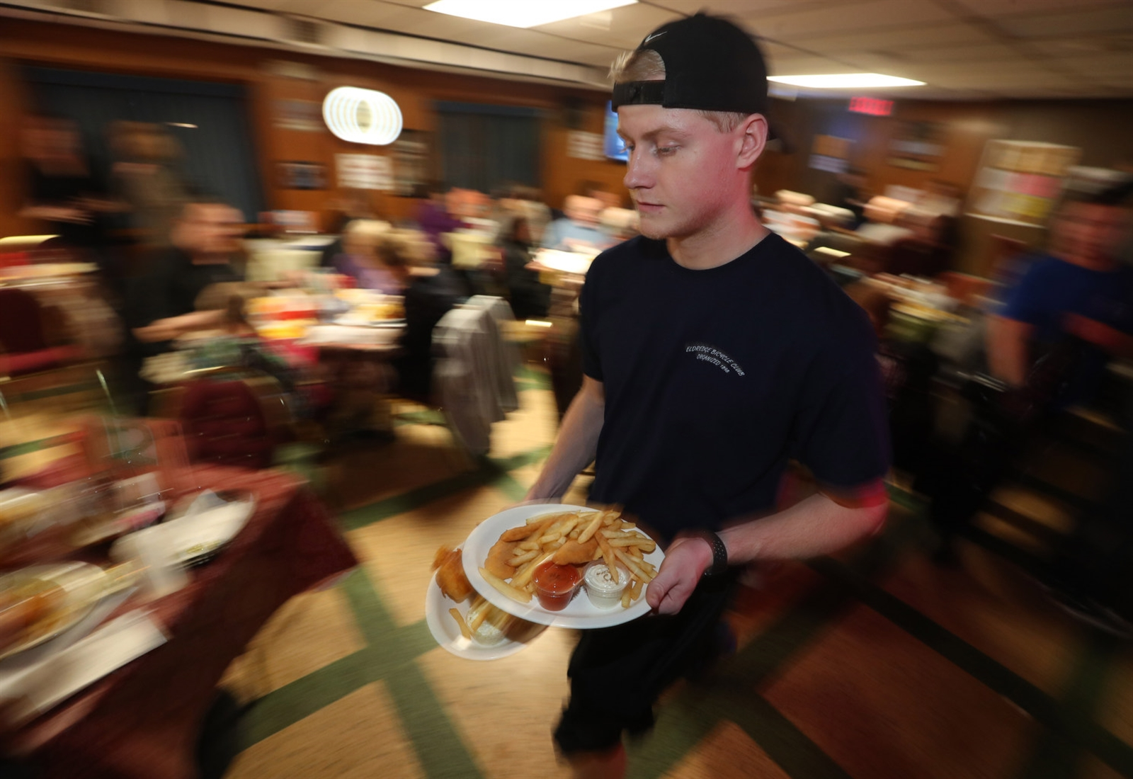 The Eldredge Bicycle Club's Charles Moore delivers fish fries to a table.