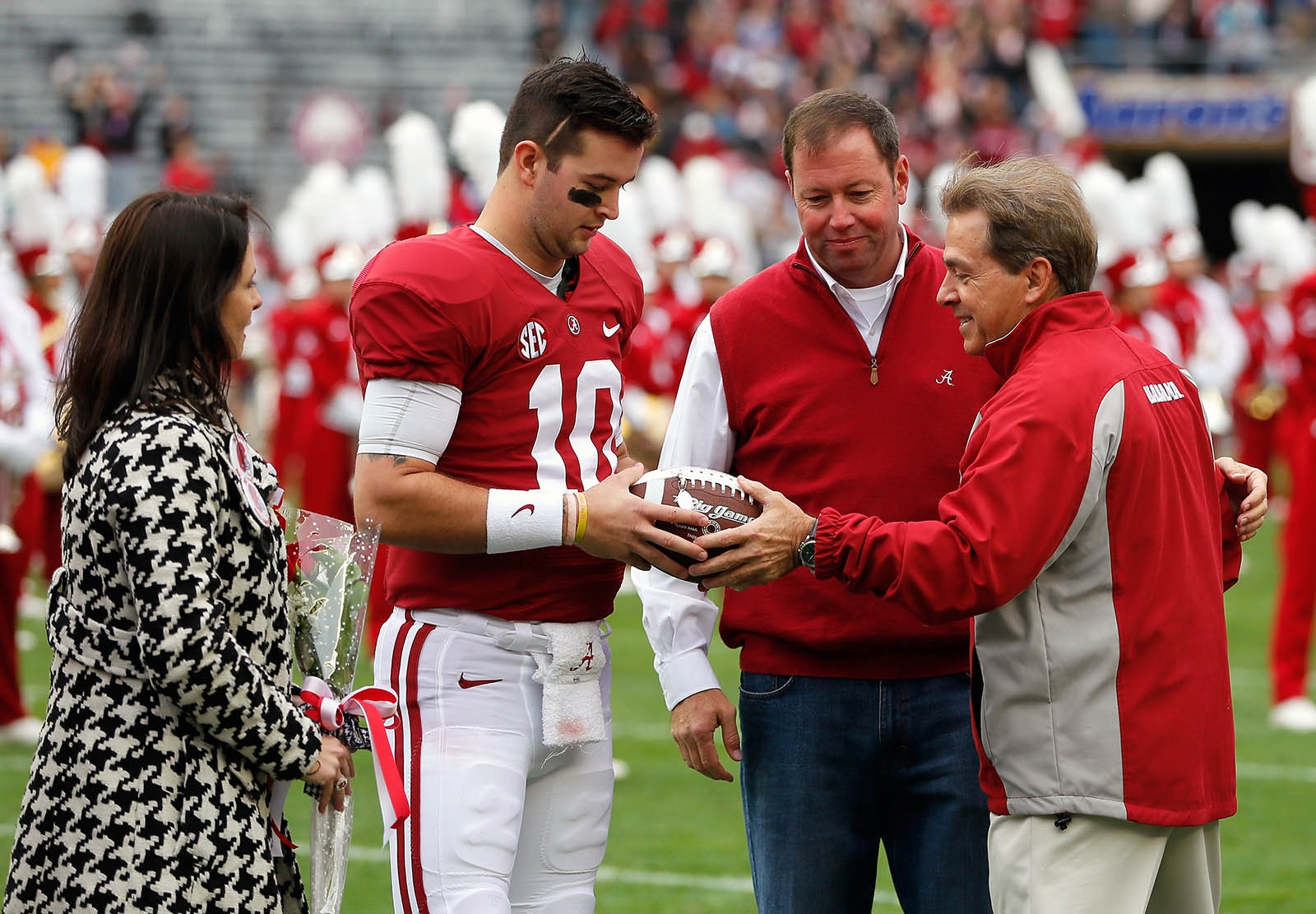 Nov. 23, 2013: AJ McCarron (10) of the Alabama Crimson Tide receives a honorary football from head coach Nick Saban during a pregame ceremony at Bryant-Denny Stadium in Tuscaloosa, Ala.