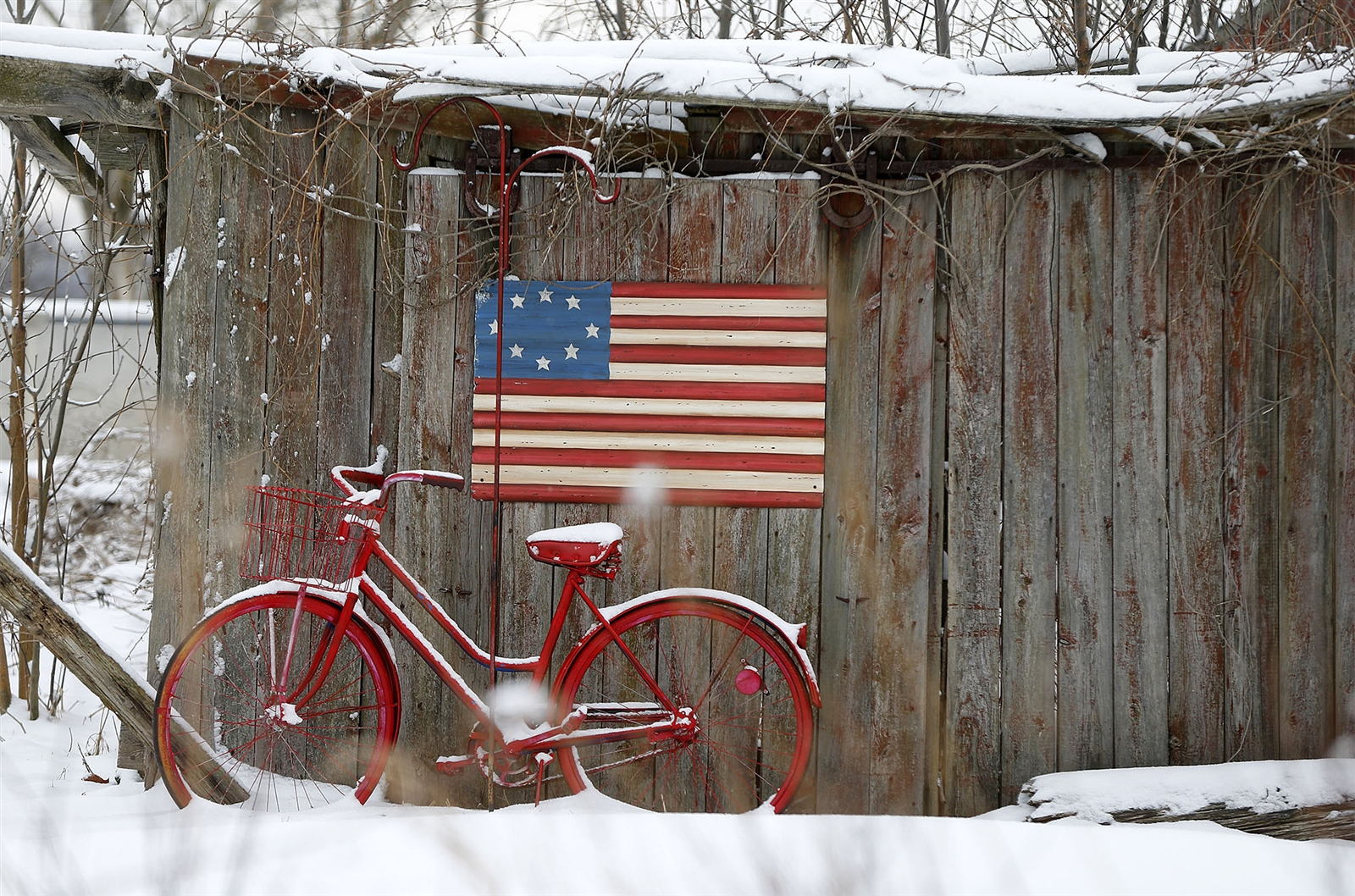 Day 73: March 17, 2018 - A red bicycle and an American flag add color to a wintry backdrop of a weather-beaten wooden fence on Lockport Road in the Town of Niagara.