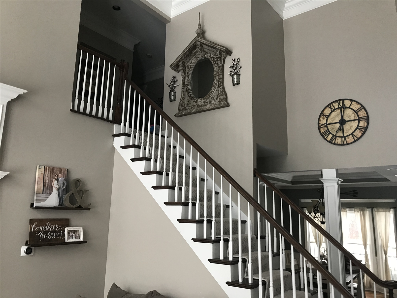 "u201cMy husband and I purchased our first home two years ago and have truly loved decorating it and making it our own,"" said Molly Dohm.  The birdhouse mirror on the staircase wall is from Tattered Tulip in Lockport."