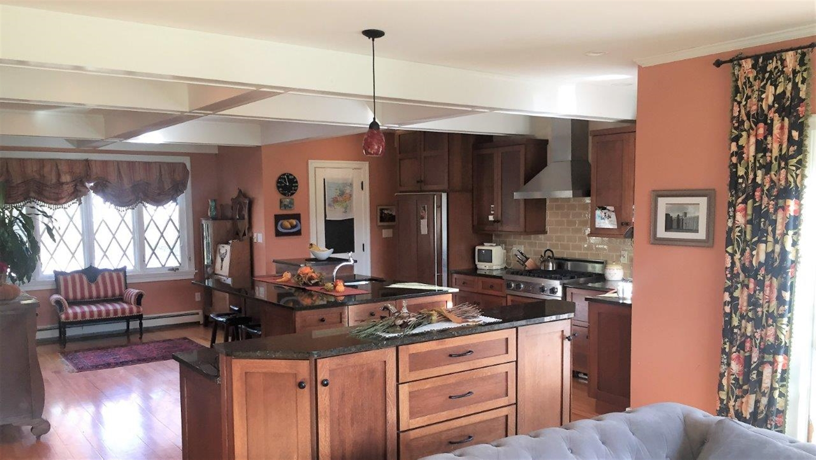 The renovated kitchen features custom quarter-sawn oak Shaker-style cabinets, granite countertops, a Viking stove and, in addition to the full-size refrigerator, two Sub-Zero paneled refrigerator drawers next to the stove. The floor is crafted from birch heartwood.