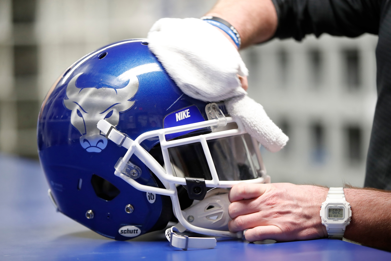 Tom Hersey, equipment manager for Buffalo Bulls football, cleans a helmet prior to the annual Blue & White Spring Scrimmage at UB Stadium on Friday, April 13, 2018.