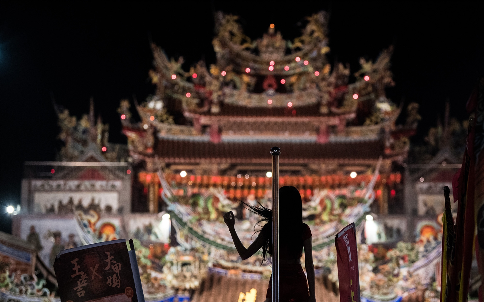 April 16, 2018 - Taiwan: A dancer performs on the roof of a car in front of Xingang Fengtian Temple, where the statue of Mazu will rest for two nights before resuming its journey nine-day Mazu pilgrimage in Xingang, Taiwan. The journey visits more than 100 temples before returning to Taichung. The centuries-old pilgrimage is now recognized by UNESCO as living heritage. With an estimated 5 million participants spread over the nine days, it is considered to be one of the greatest religious festivals in the world.