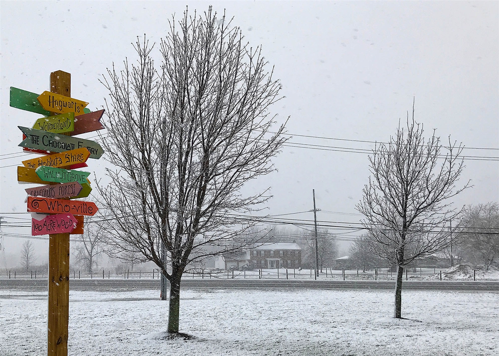 Day 106: April 17, 2018 - A brightly painted sign post in front of the Clarence Public Library stands out against a late spring snow.
