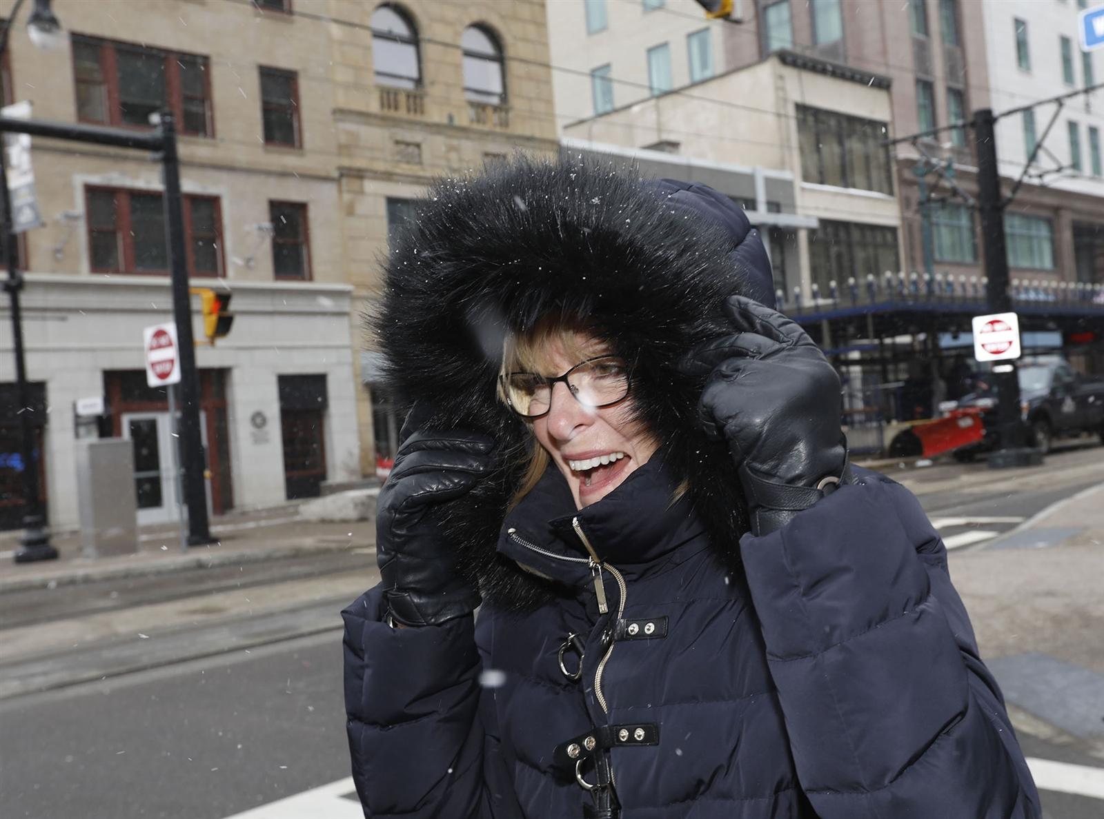 Trish Scarcello braces herself against the snow as she walks down Main Street in Buffalo.