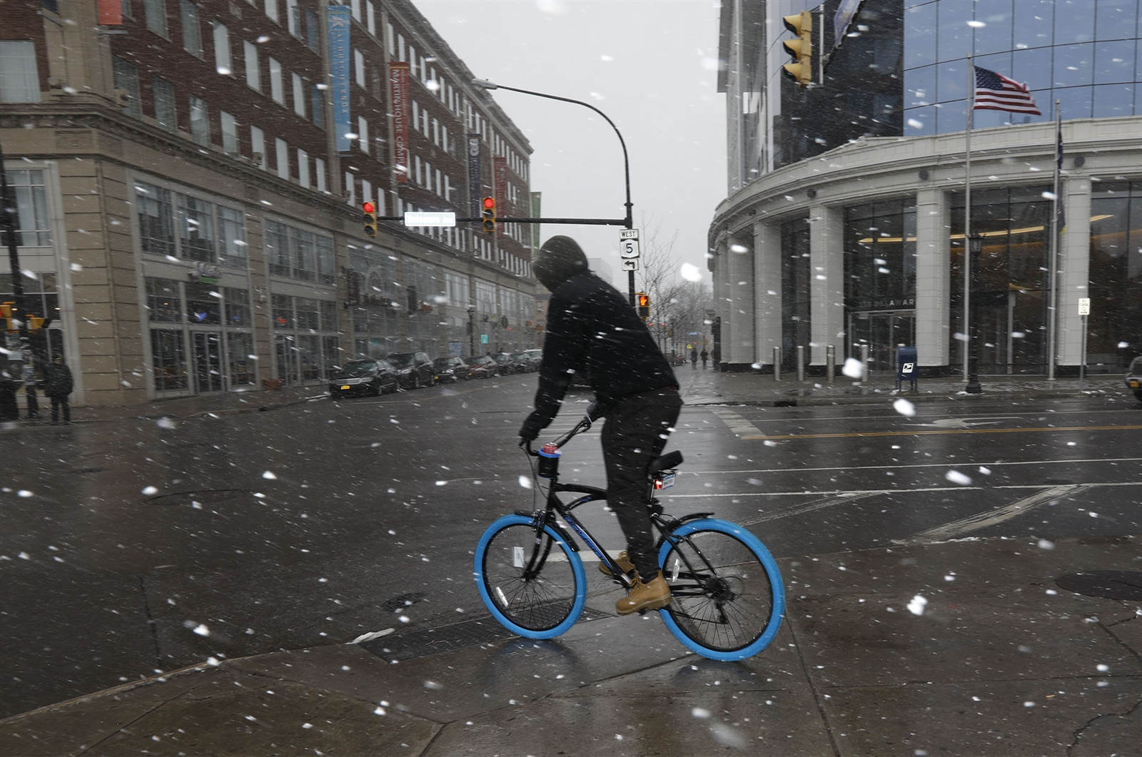 A cyclist rides off the sidewalk at Delaware and Chippewa as heavy snow falls in Buffalo on Tuesday.
