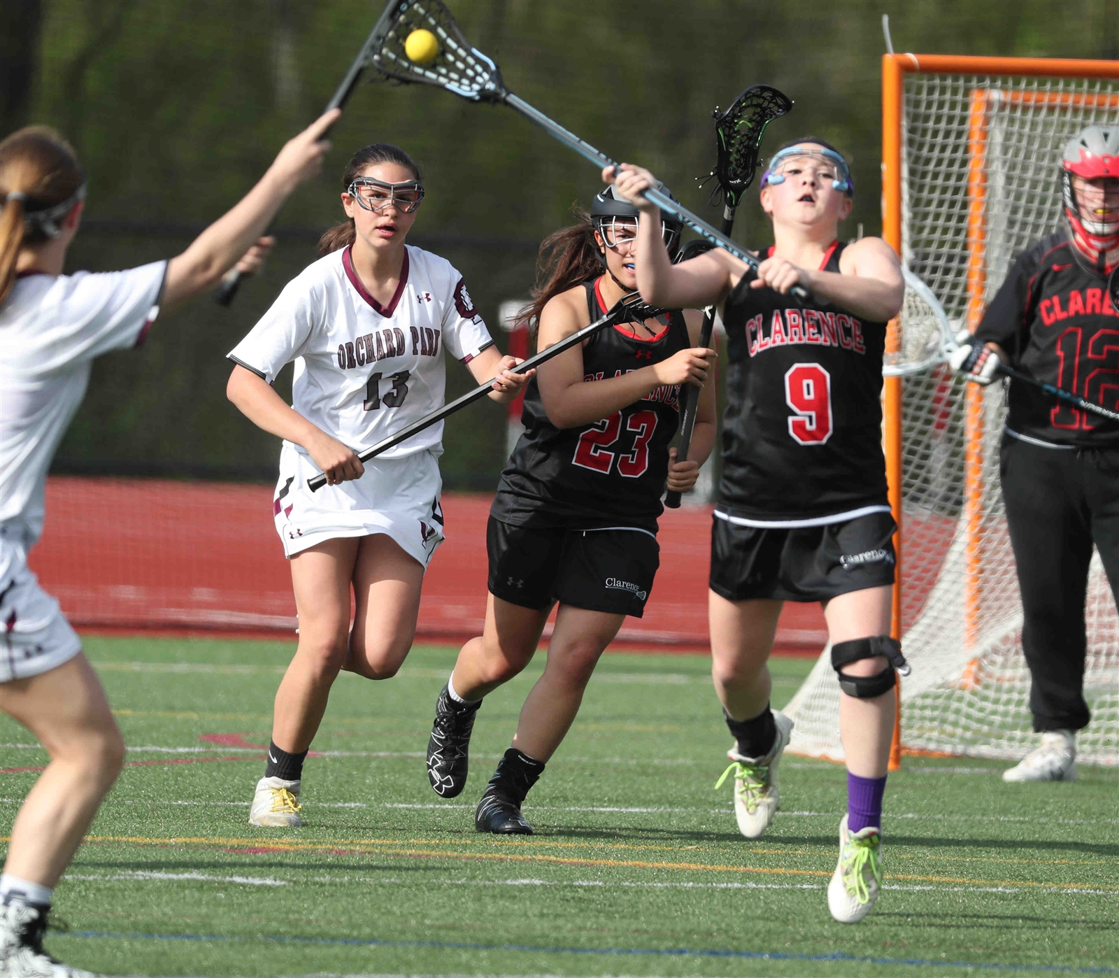 Madison Leeper of Clarence passes the ball past Jessica Peters of Orchard Park up the field.