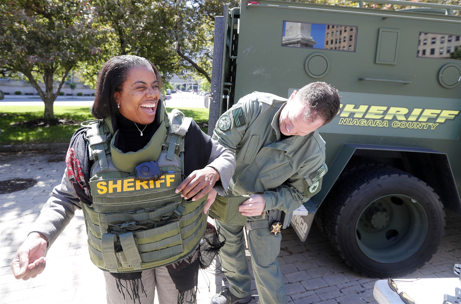 Niagara County Sheriff Deputy Tom Huff has Deidre Joseph from Tampa, Fla., try on a ballistic vest during an outdoor showcase of area law enforcement equipment in Niagara Square in Buffalo Wednesday, June 7, 2017.