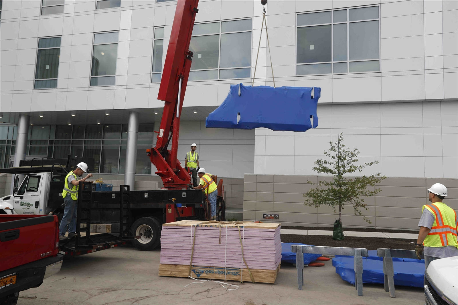 Shrink-wrapped blue letters being unloaded and installed on north side of new Oishei Children's Hospital.