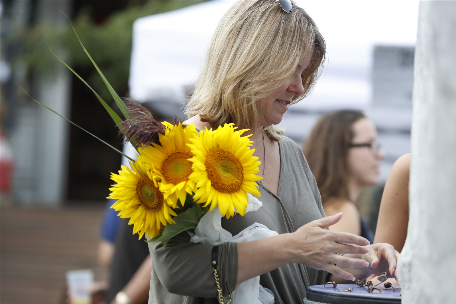 Michele Dill tries on some jewelry during the Elmwood Avenue Festival of the Arts in Buffalo Saturday, August 26, 2017.