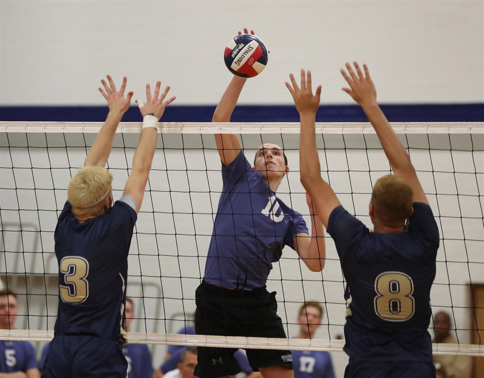 Matthew Logel, of Grand Island, kills the ball past Alexander Stoj, left, and Solomon Shabazz, of Sweet Home.