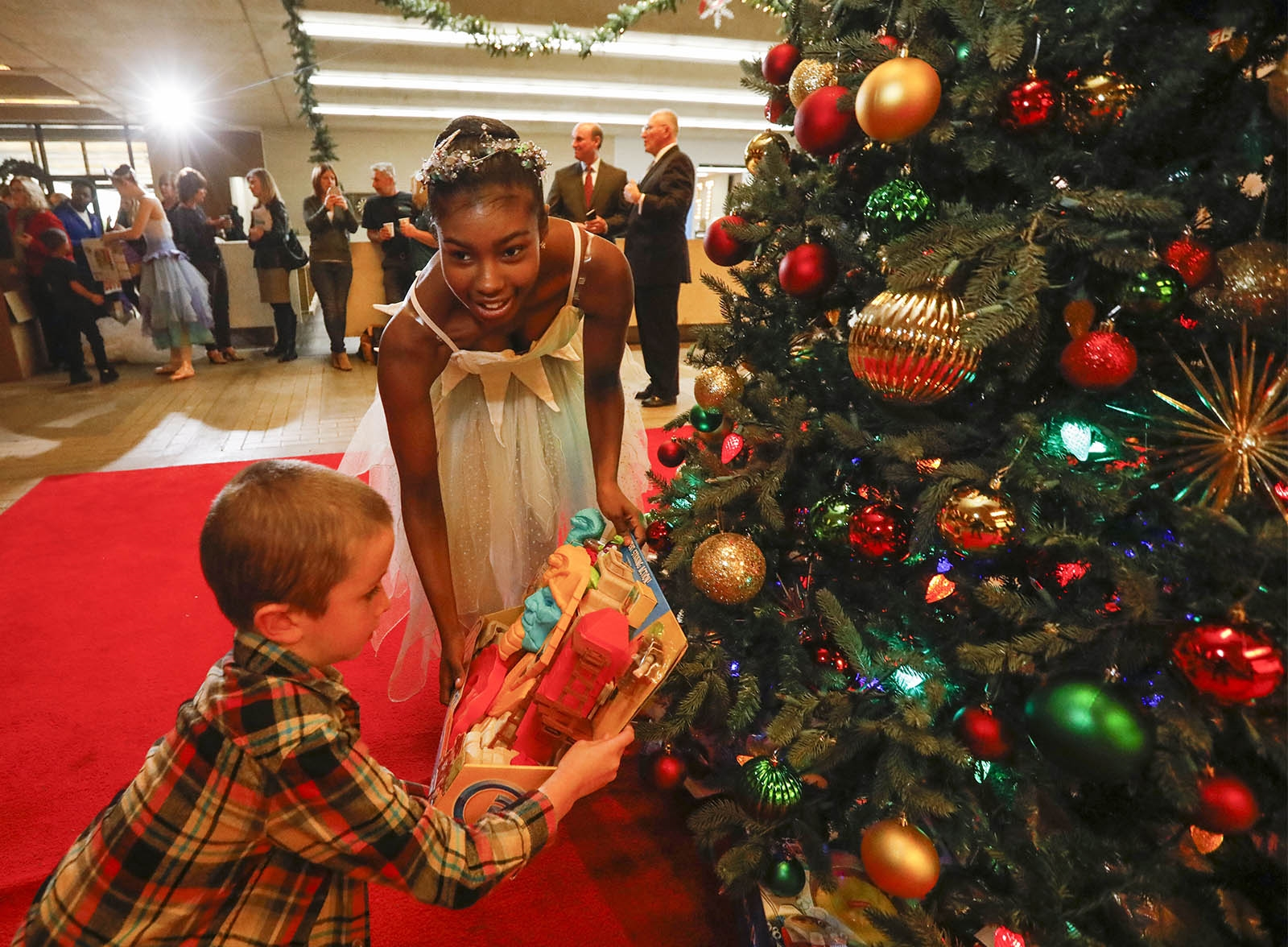 Houghton Academy kindergarten student Owen Geiger, 5, and Neglia Ballet dancer Amirah Muhammad, 16, help place presents under the tree during the kickoff of the annual News Neediest drive in the lobby of The Buffalo News.