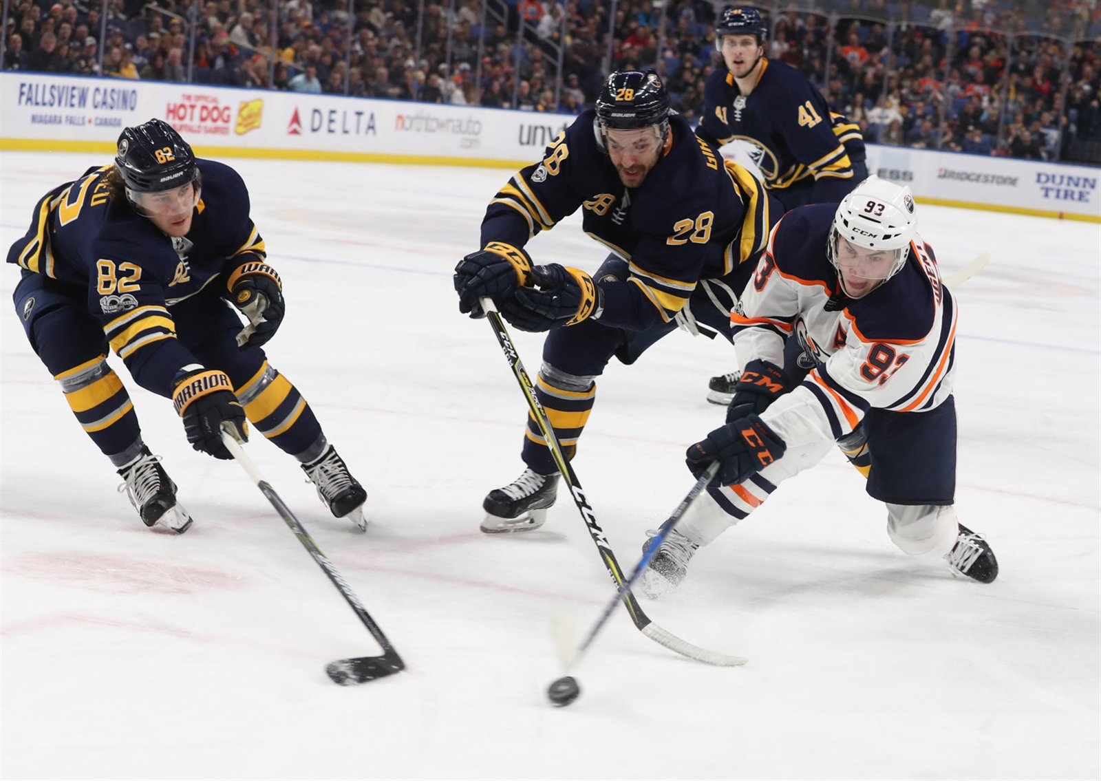 Nathan Beaulieu, left, and Zemgus Girgensons defend in the Sabres zone againts Ryan Nugent-Hopkins of Edmonton.