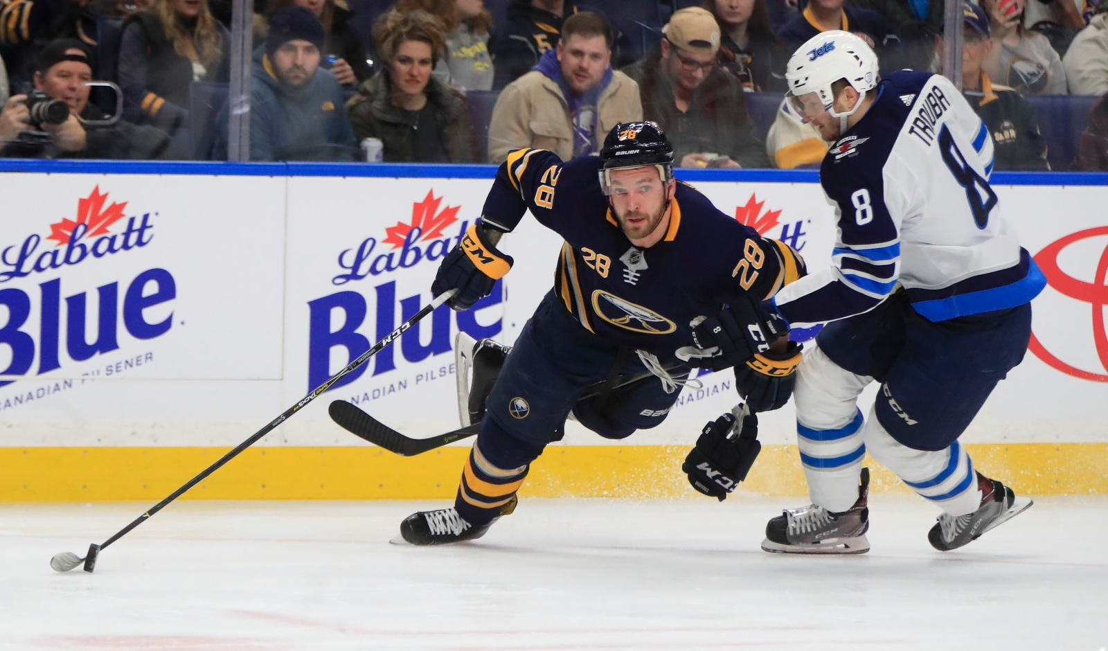 Buffalo Sabres' Zemgus Girensons is hooked by Winnipeg Jets' Jacob Trouba during first period action.