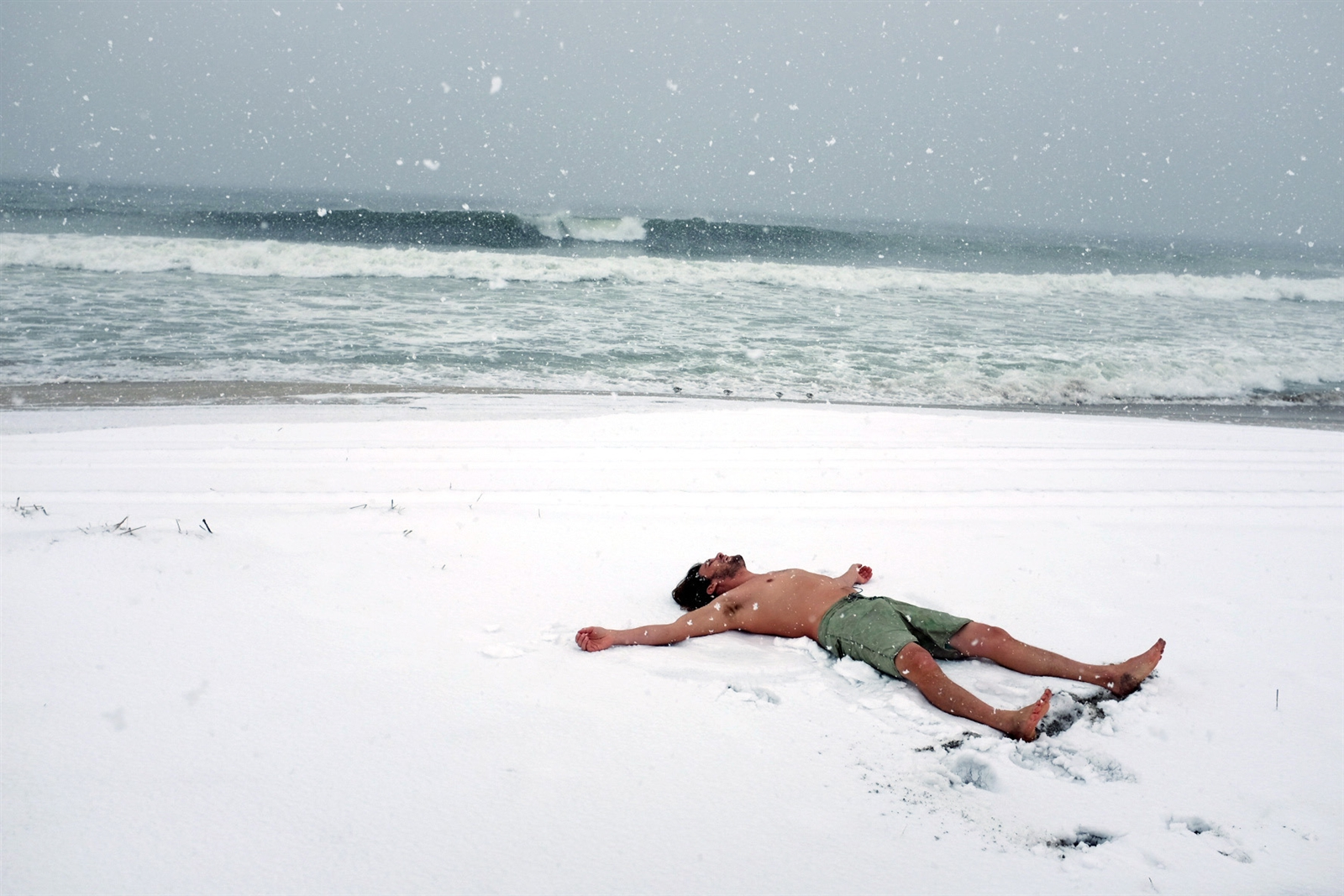 obby Reynolds lies on the snowy beach before surfing at Rockaway Beach during a snow storm March 21, 2018 in the Queens borough of New York.  New York City and much of New England has experienced four Nor'easter winter storms in recent weeks.