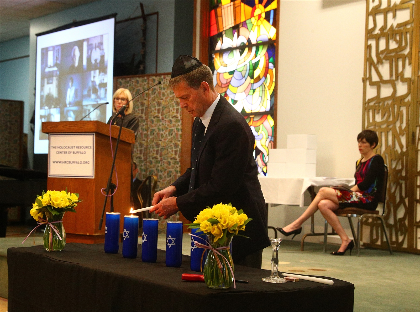 Peter Forgach lights a candle at the 2018 Yom HaShoah Commemoration.